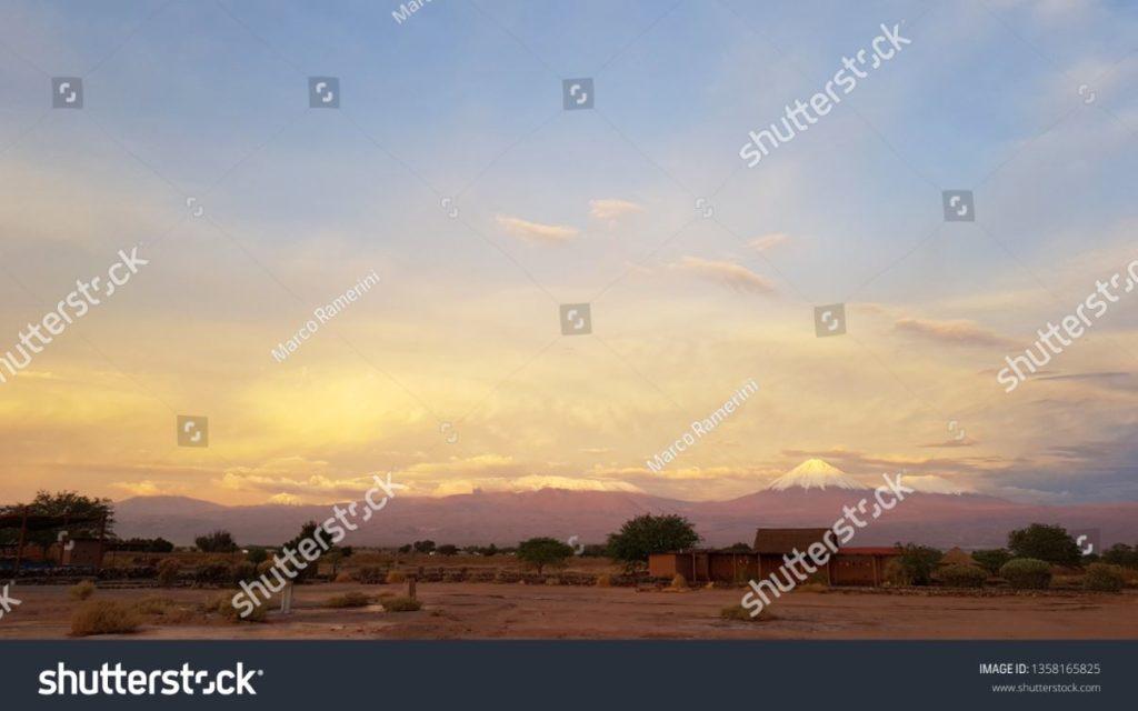 Luci del tramonto nel paesaggio arido e desolato del deserto di Atacama con le cime dei vulcani innevati della cordigliera delle Ande sullo sfondo. Autore e Copyright Marco Ramerini